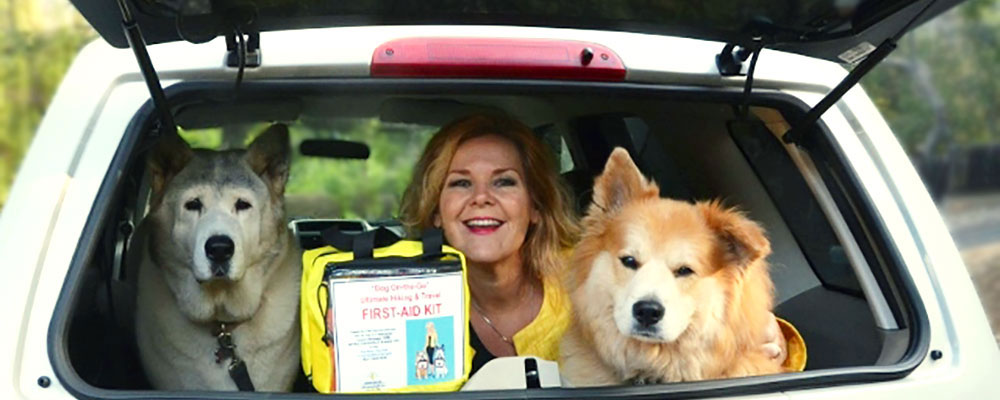 Denise Fleck with her two dogs and a pet first aid kit in car trunk