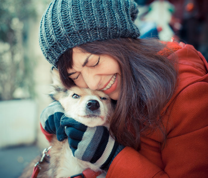 woman in winter gear hugging dog
